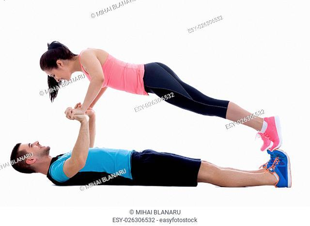 Two fitness trainers doing a face to face push-up while smiling. Image isolated on white background