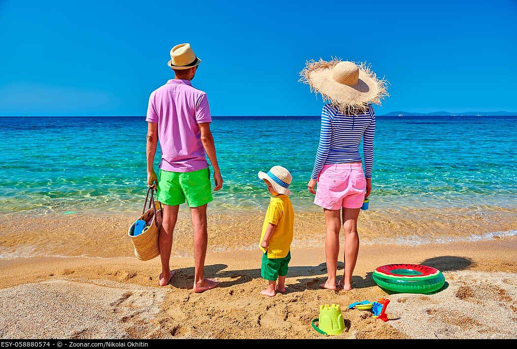 Family on beach wearing straw sun hat. Young couple with three year old boy, inflatable ring, beach bag and toys. Clear sky. Summer family vacation. S...