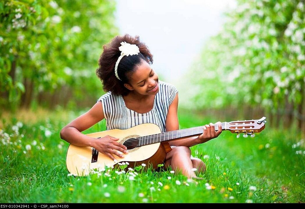 Outdoor portrait of a young beautiful african american woman playing guitar - Black people
