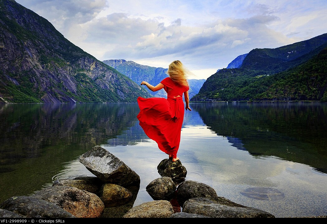 Blonde girl in a red dress moved by the wind standing on a rock in front of a lake, Eidfjord, Hordaland, Norway.