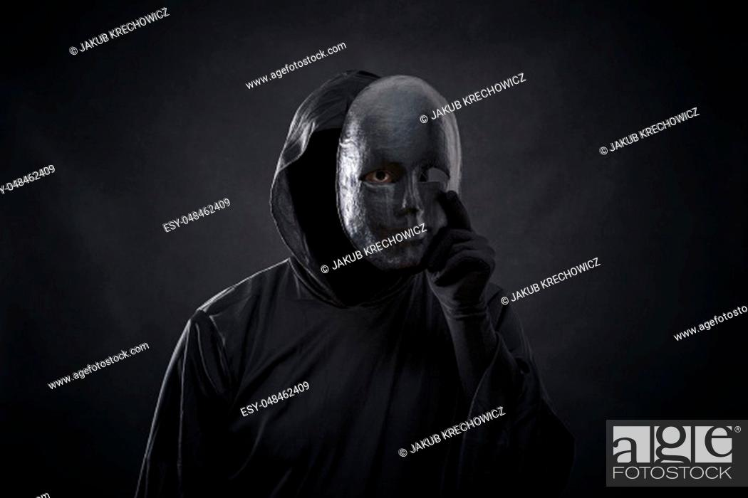 Stock Photo: Scary figure in hooded cloak with mask in hand.