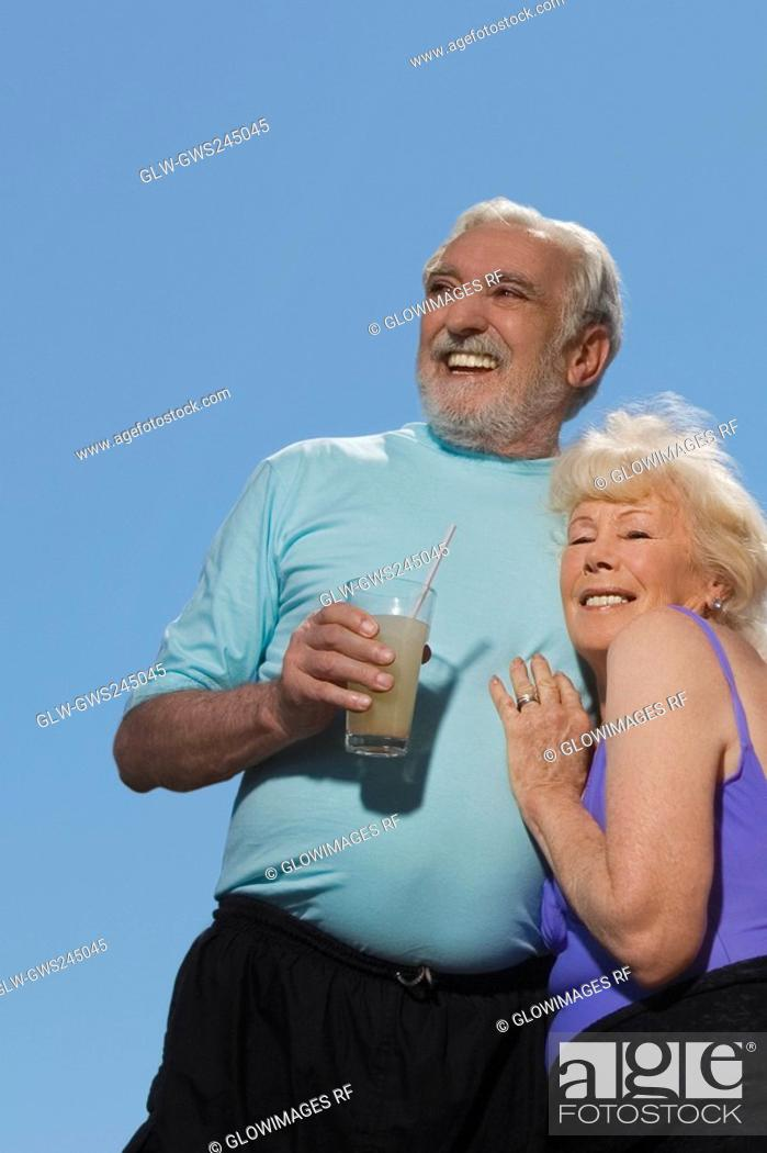 Stock Photo: Low angle view of a senior couple embracing each other.
