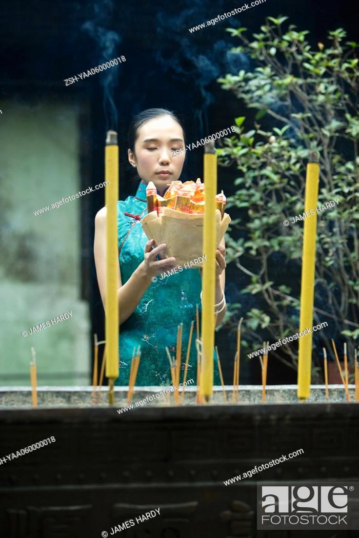 Stock Photo: Young woman dressed in traditional Chinese clothing holding up religious offering near burning incense.