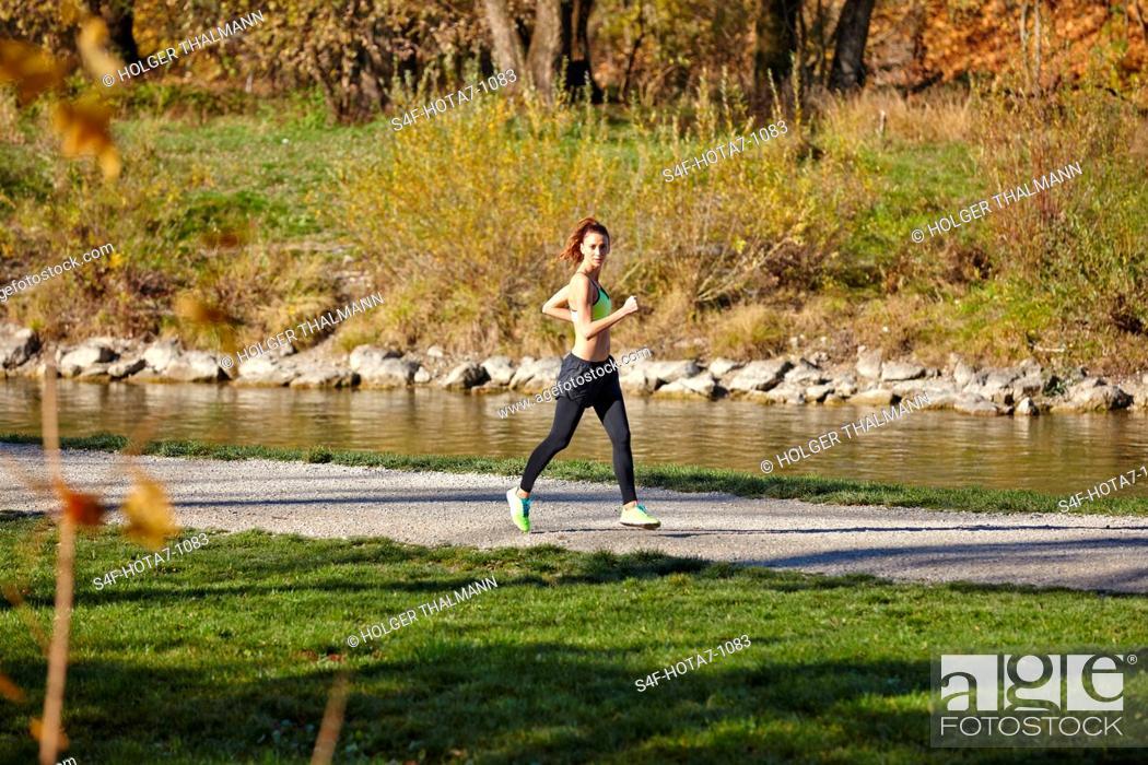 Stock Photo: Frau joggt am Flussufer.