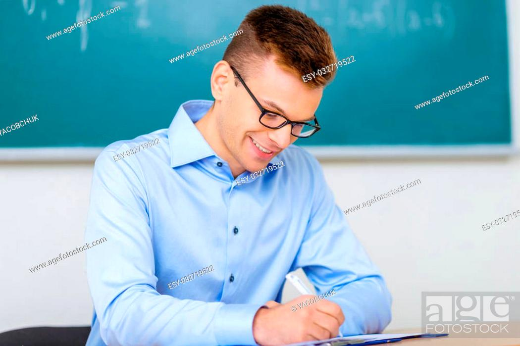 Stock Photo: Paperwork. Smiling male professor sits at the desk while filling in his journal.