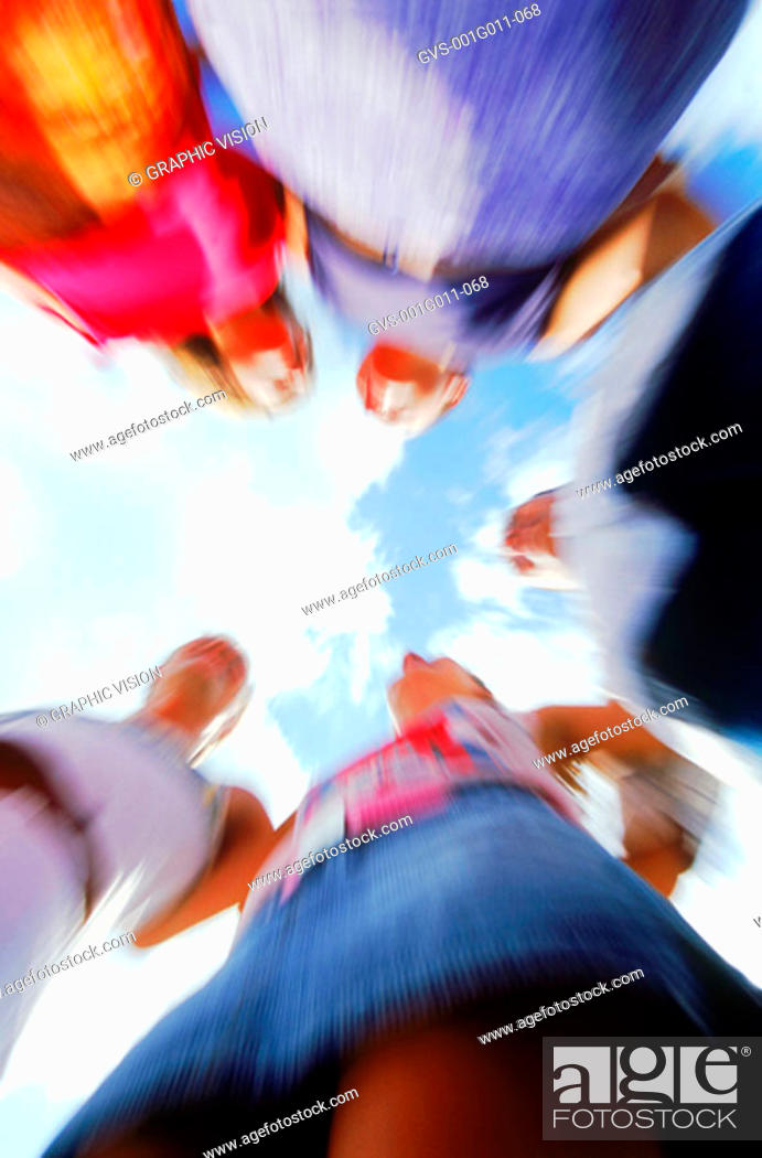 Stock Photo: Low angle blurred view of a group of young people standing in a circle.