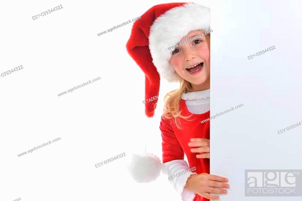 Photo de stock: little girl in red santa hat peeking from billboard.