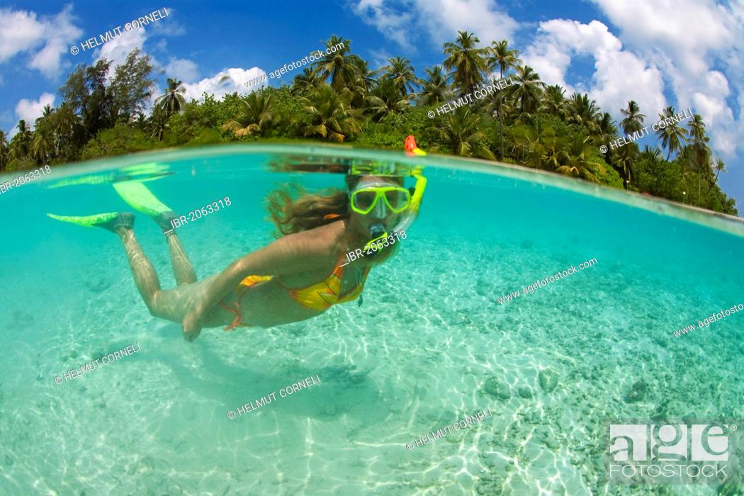 Stock Photo: Image, half above, half under water, young woman snorkeling in the lagoon of Biyadhoo Island, South Male Atoll, Maldives, Indian Ocean, Asia.
