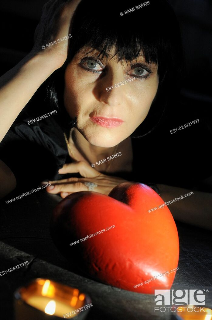 Stock Photo: Mature woman looking pensive with a heart shape - looking for love concept.