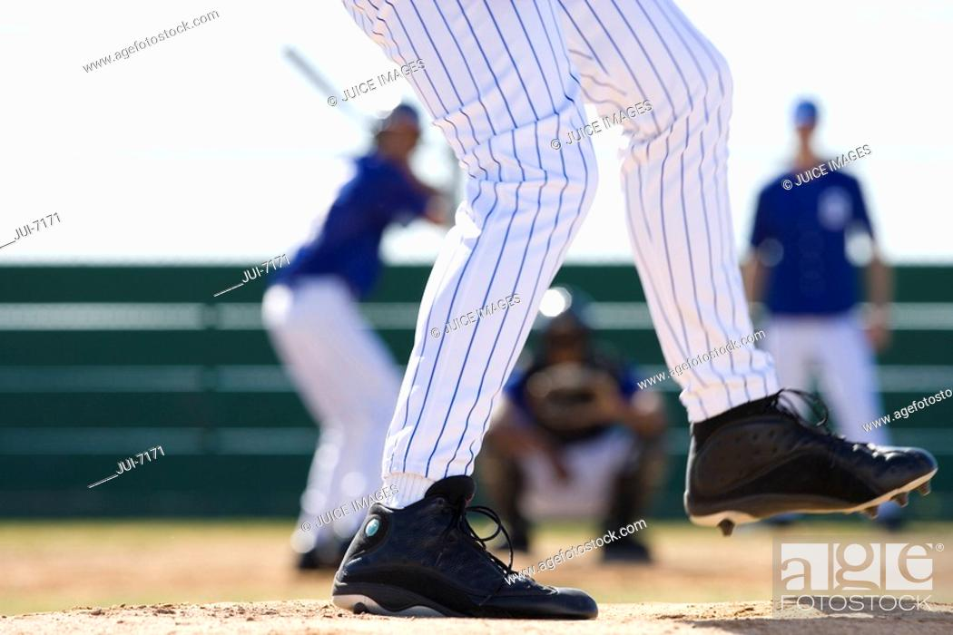 Stock Photo: Young men playing baseball, focus on pitcher in foreground, low-section, rear view.