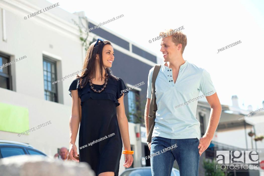 Stock Photo: Smiling young couple looking at each other while walking.