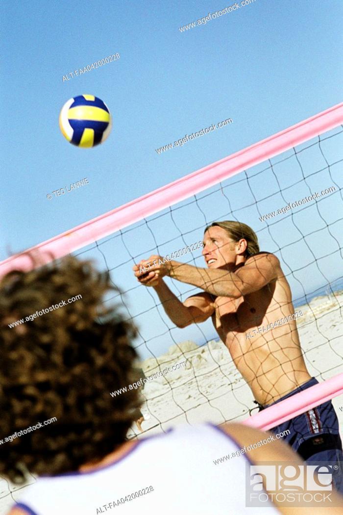 Stock Photo: Male playing beach volleball, preparing to hit ball.