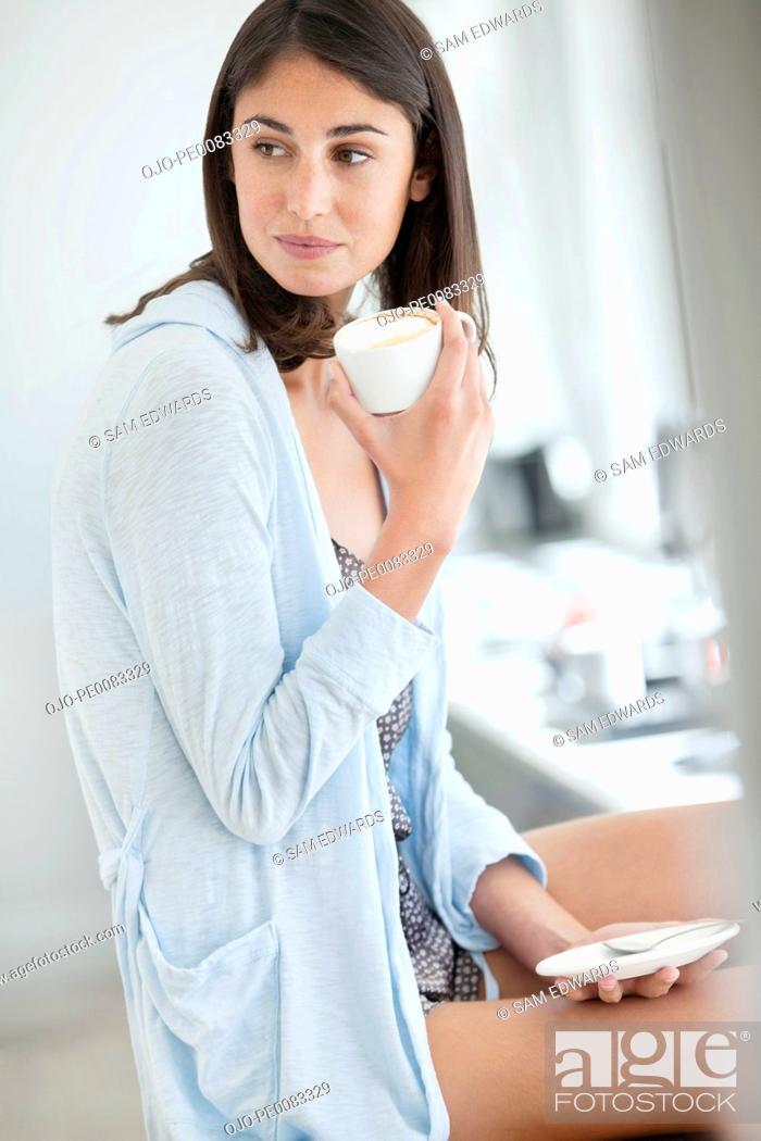 Stock Photo: Woman drinking coffee in pajamas.