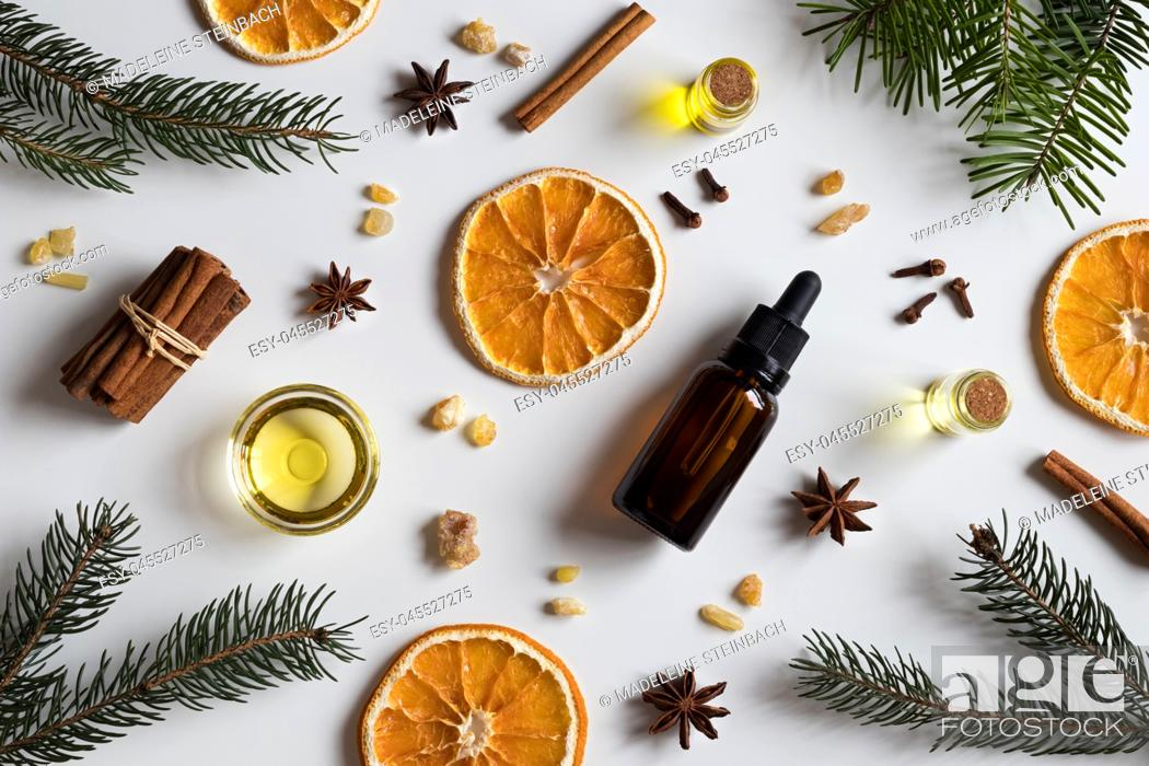 Stock Photo: Selection of essential oils with Christmas spices and ingredients on white background: bottles of essential oil, spruce, fir, frankincense resin, star anise.
