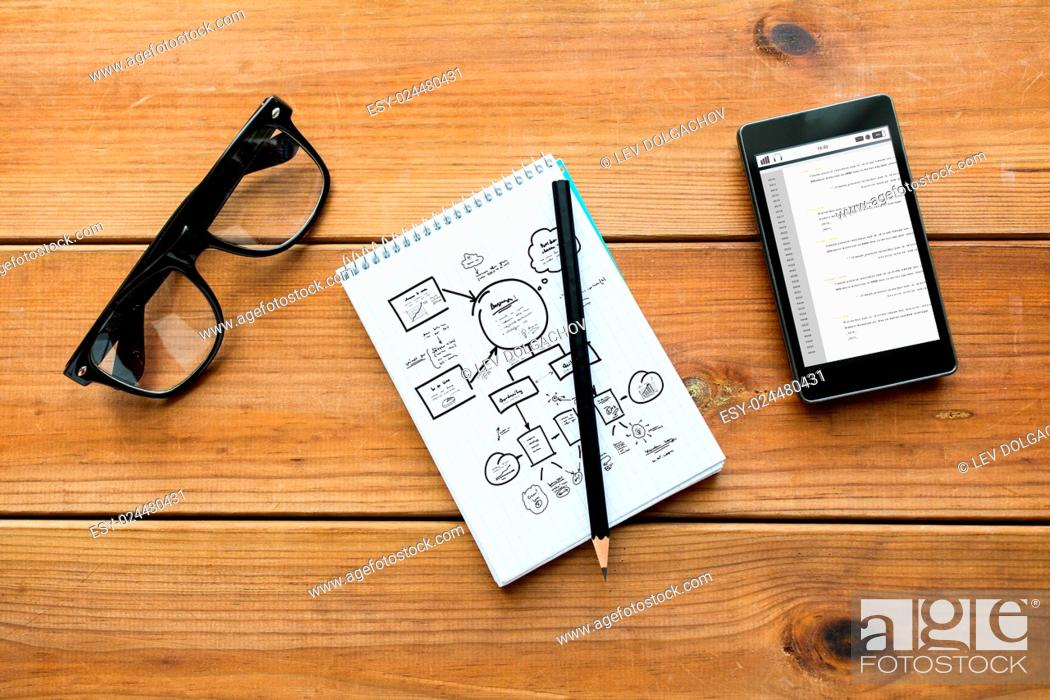 Stock Photo: planning, education, business and technology concept - close up of scheme drawing in notepad with pencil, with coding on smartphone and eyeglasses on wooden.