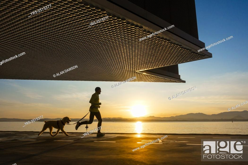 Stock Photo: Santander, Cantabria, Spain. Jogger with dog at sunrise under Centro Botín art gallery, designed by Pritzker Prize-winner architect Renzo Piano.