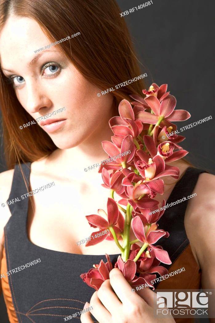 Stock Photo: portrait of a woman with cymbidium orchids.