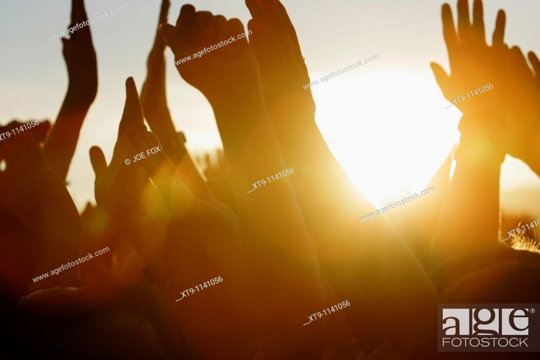 Stock Photo: sun setting at open air concert through fans waving their arms in the air.