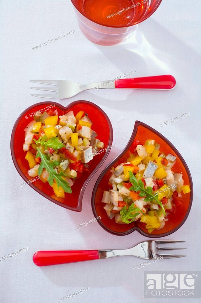 Stock Photo: Herring salad in red heart-shaped dishes.