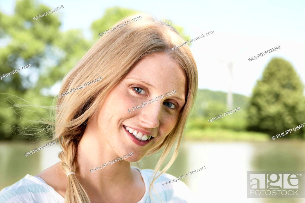 Stock Photo: Germany, Cologne, Young woman smiling, portrait, wind turbine in background.