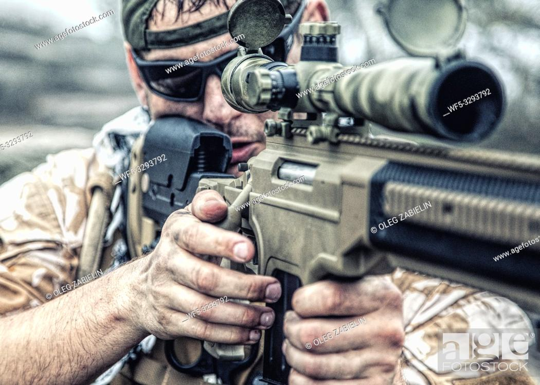 Stock Photo: Private military contractor PMC sniper in baseball cap with assault rifle in the rocks.