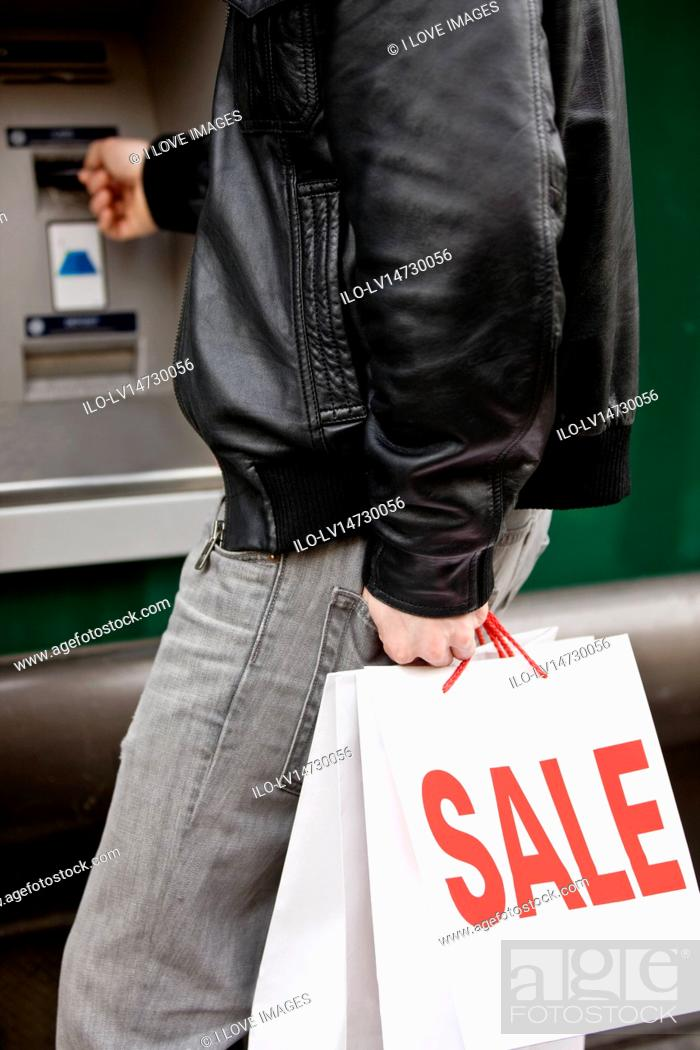 Stock Photo: A young man using a cash machine, holding carrier bags.
