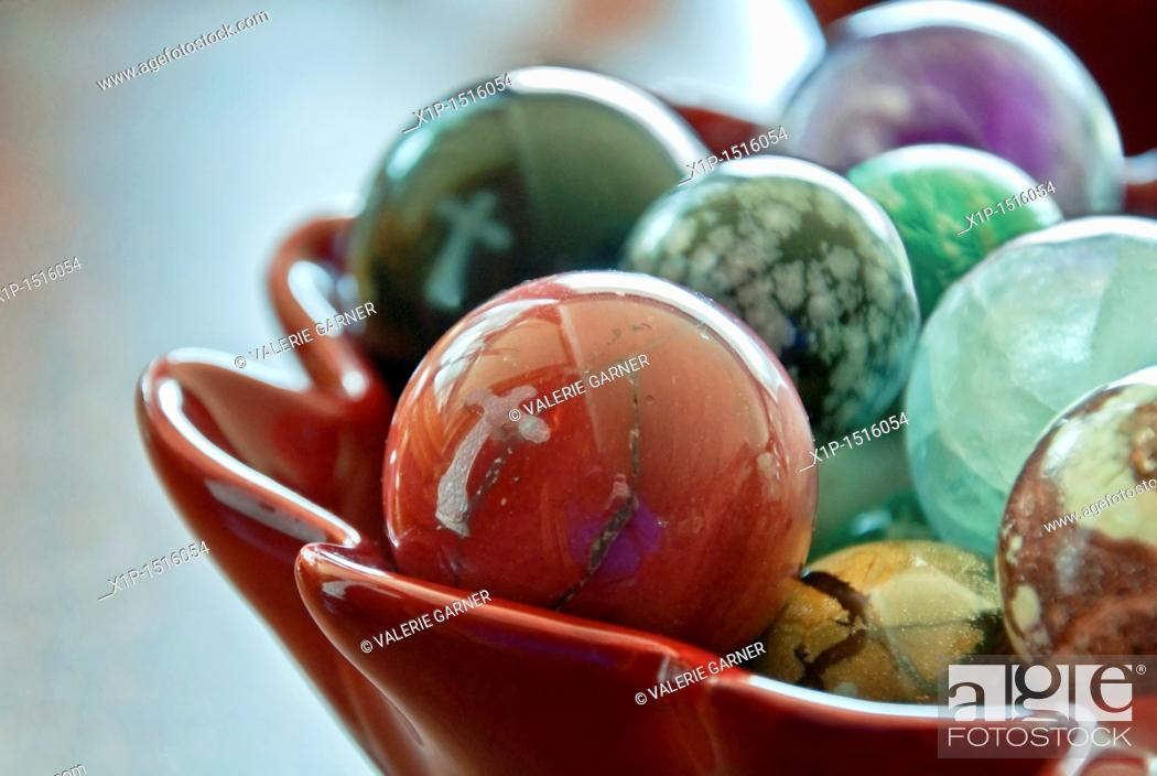 Stock Photo: This stock image shows two white crosses reflected in a bowl of large, glass marbles  Background intentionally blurred for artistic effect.