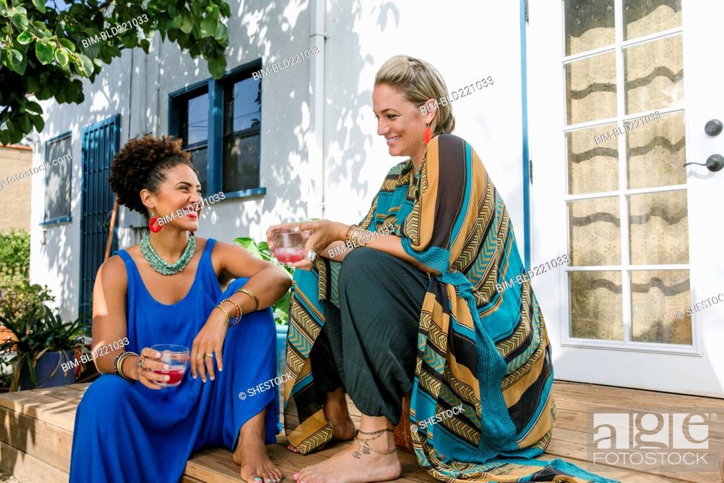 Stock Photo: Women drinking juice on front stoop.