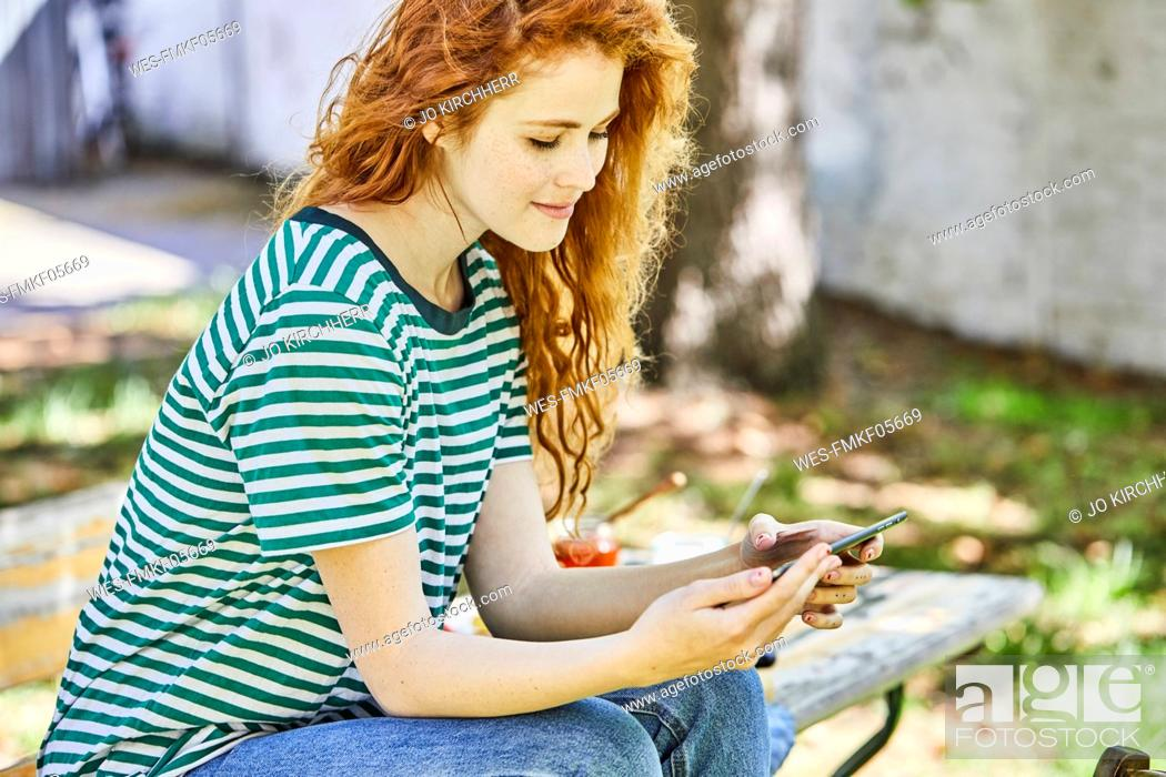 Stock Photo: Smiling redheaded young woman sitting on bench in the garden looking at cell phone.