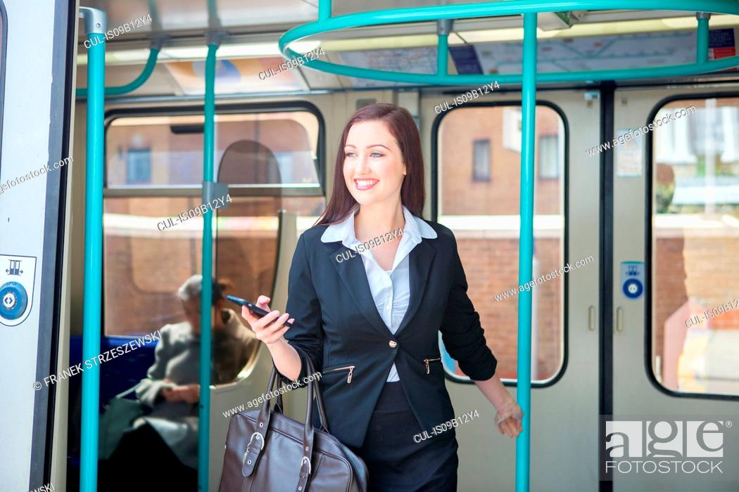 Stock Photo: Businesswoman travelling in Docklands Light Railway train, London.
