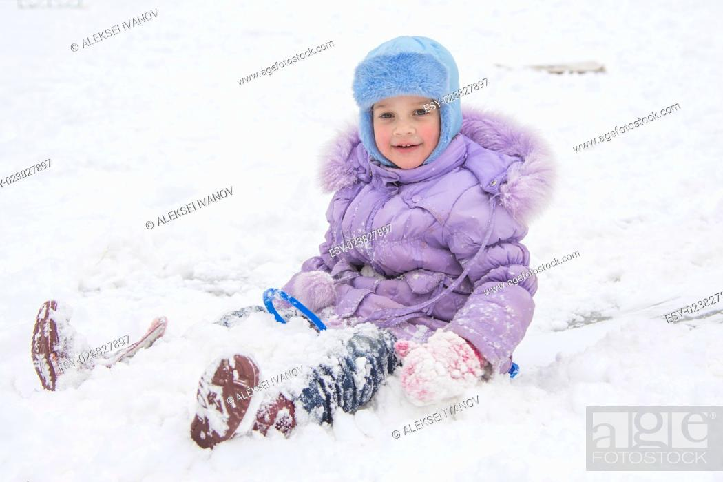Stock Photo: Five-year girl riding on a snowy icy hill.