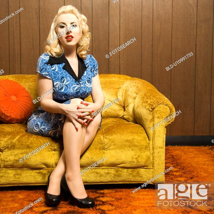 Stock Photo: Attractive Caucasian woman sitting on retro style couch.