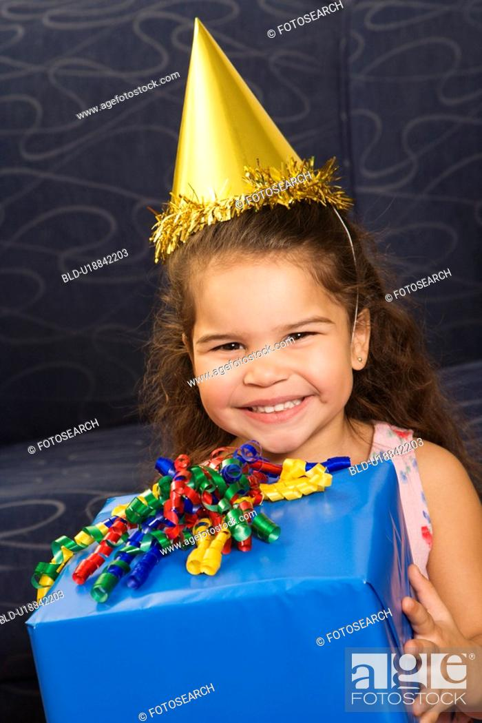 Stock Photo: Girl wearing party hat holding birthday present smiling and looking at viewer.