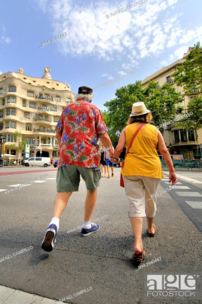 Stock Photo: Couple walking. Mila house aka 'La Pedrera' 1906-1912. 261-265 Provença street. Architect Antoni Gaudí. Barcelona. Catalonia. Spain.