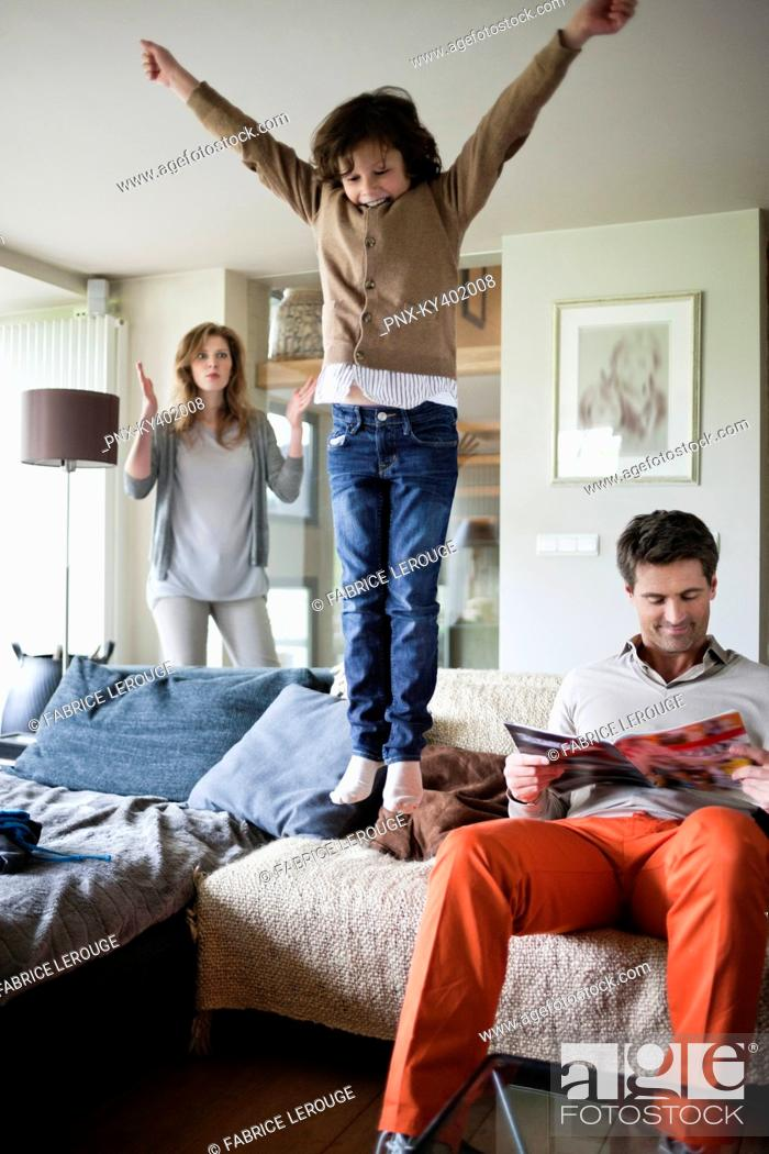 Stock Photo: Naughty boy jumping on couch with his parents at home.