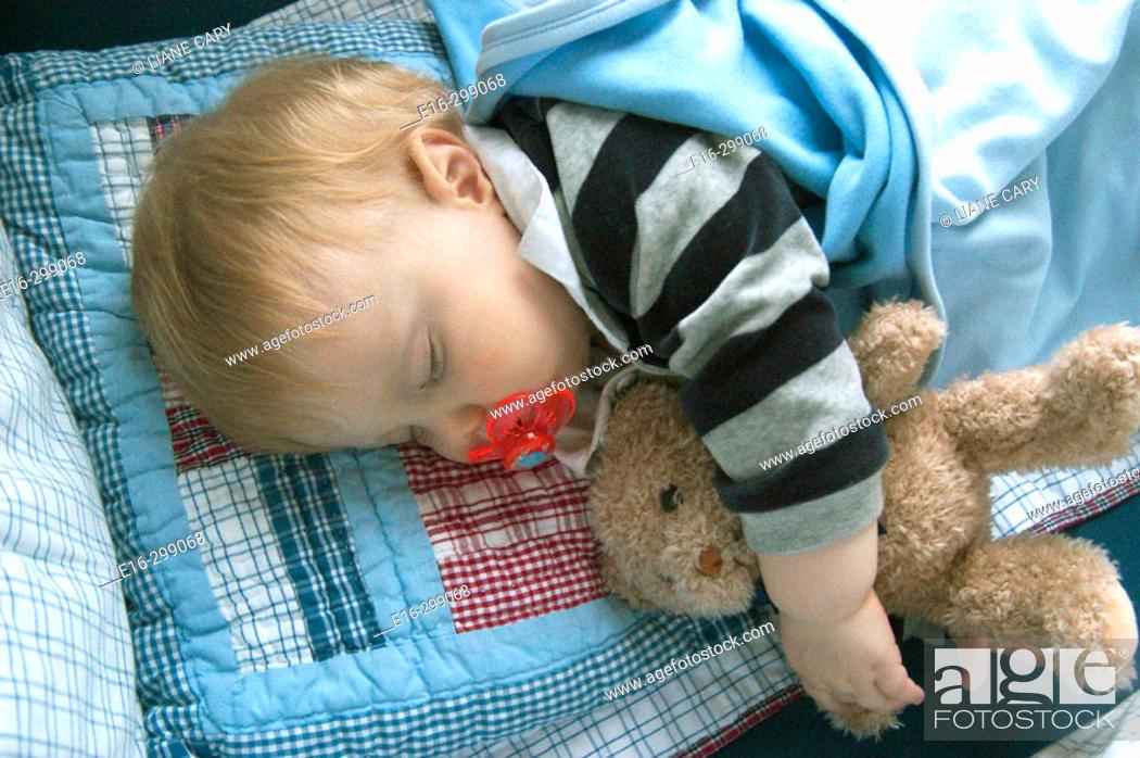 Stock Photo: baby sleeping with teddy bear.