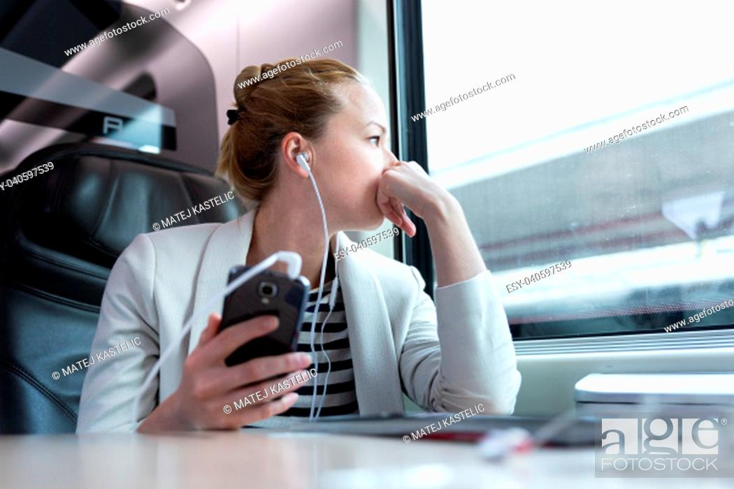 Stock Photo: Thoughtful businesswoman looking trough the window, listening to podcast on cellphone using headphone set while traveling by train in business class seat.