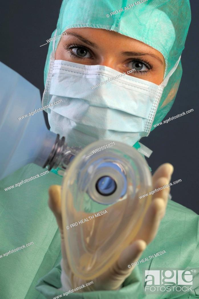 Imagen: young woman with respiratory mask and ambu bag in an operation room. She is wearing a mouth mask and a bonnet.