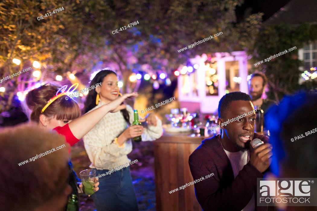 Stock Photo: Friends drinking and singing karaoke at party.