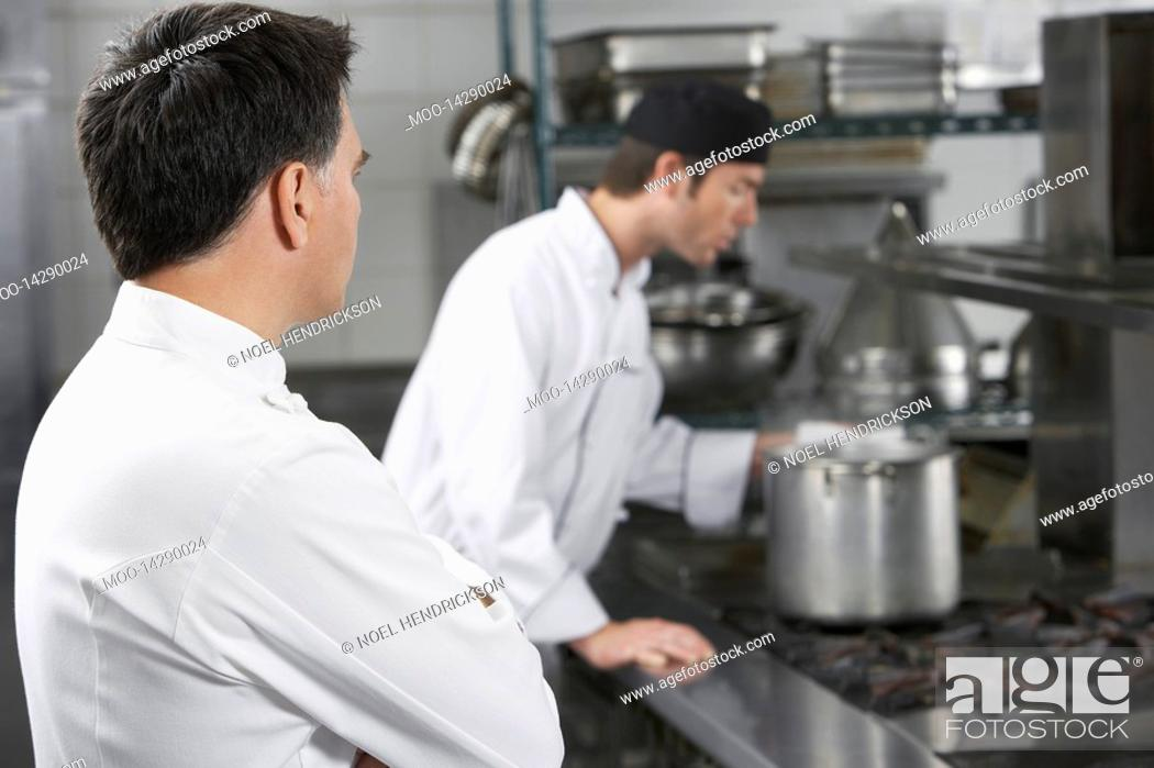 Stock Photo: Two male chefs working in kitchen.