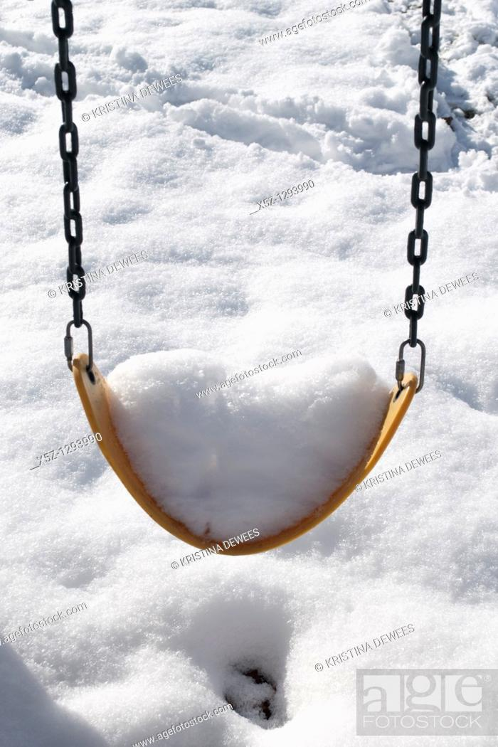 Stock Photo: A swing full of snow in the Winter.