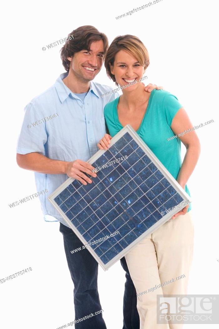 Stock Photo: Couple holding solar panel.