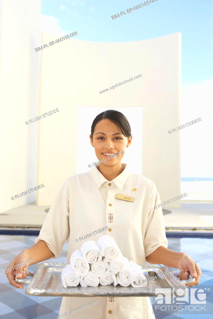 Stock Photo: Hotel employee holding silver tray with rolled up towels, Los Cabos, Mexico.