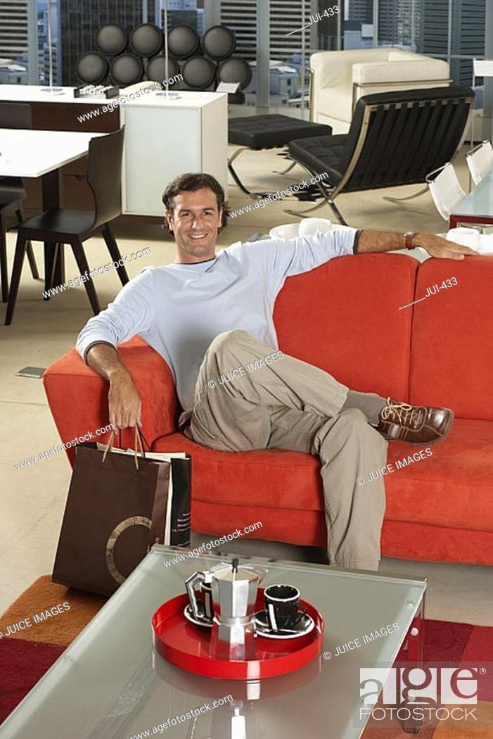 Stock Photo: Man with shopping bags sitting on new red sofa in furniture store, smiling, portrait.