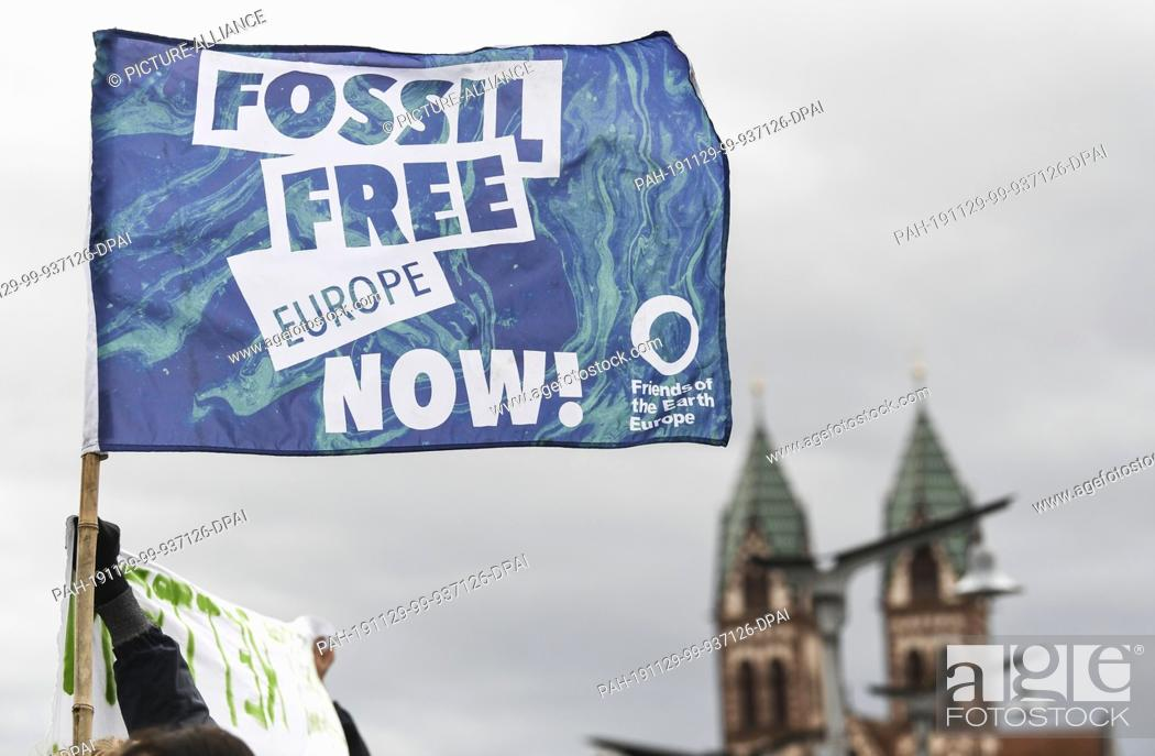 """Stock Photo: 29 November 2019, Baden-Wuerttemberg, Freiburg: At the action day of """"""""Fridays for Future"""""""" a flag with the inscription """"""""Fossil free Europe now!"""""""" is flying in."""