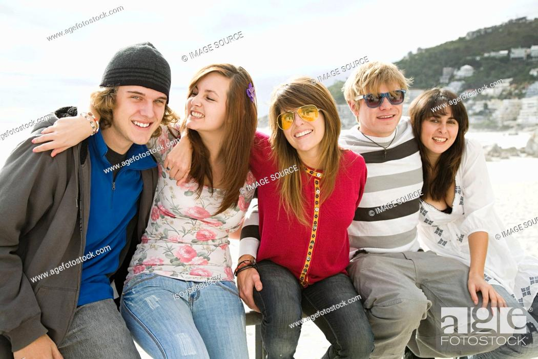 Stock Photo: Group of friends sitting on railings.