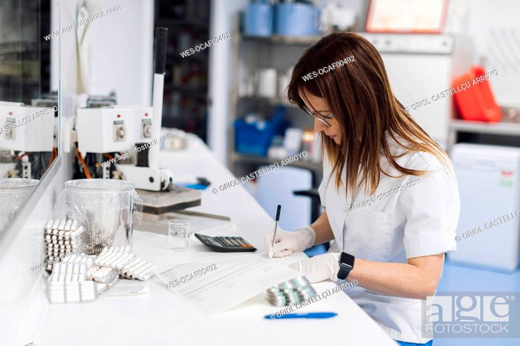 Imagen: Confident female scientist writing data at desk in laboratory.