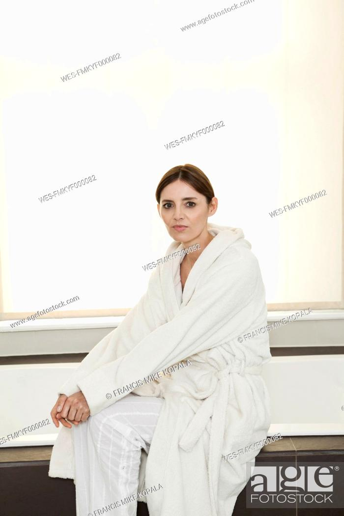 Stock Photo: Germany, Berlin, Mature woman sitting on bathtub, portrait.