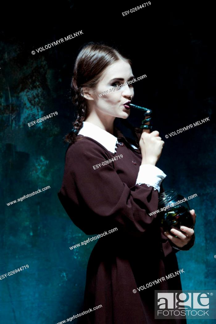Stock Photo: Portrait of a young girl with snakes. Girl in school uniform as killer. The image in the style of Halloween.