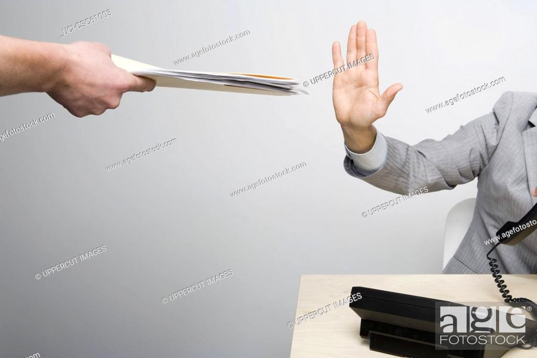 Stock Photo: Businessman holding hand up to paperwork.